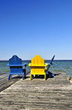 Chairs on wooden dock at lake Stock Photo