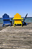 Chairs on wooden dock at lake Stock Images