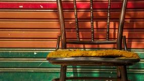 Chaise abandonnée en métal de vintage avec la porte colorée de volet de rouleau photographie stock libre de droits