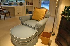 Chaise in bedroom office. Blue chaise with gold pillow and wastebasket in bedroom office, showing swimming pool through glass door stock images