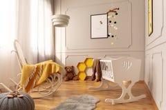 Chaise blanche de berceau et de basculage avec la couverture jaune confortable dans la pièce grise lumineuse d'enfant en bas âge image stock