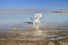 Chaise blanche en plastique dans l'eau de la mer morte Images libres de droits