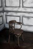 Chaise brun-grise de vintage se tenant près du mur Photo stock