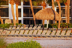 Chaise chairs on beach. Chaise lounge chairs and thatched umbrella on beach outside condominium in Sanibel Island, Florida stock images