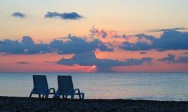 Chaise -chaise-longues twee op strand bij mooie zonsopgang Royalty-vrije Stock Fotografie