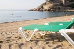 Chaise-chaise-lounge sulla spiaggia abbandonata a Tossa de Mar Fotografia Stock
