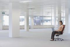 Chaise d'Using Laptop On de femme d'affaires dans le bureau vide Image stock
