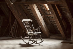 Chaise de basculage en bois dans le grenier photos stock