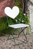 Chaise de jardin avec le dossier de forme de coeur sur le pavé rond avec le flowe Image libre de droits