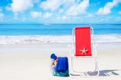 Chaise de plage avec des étoiles de mer et sac par l'océan Photo stock