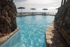 Chaise de plage avec le parapluie sur le pool privé, vue d'océan Photo libre de droits