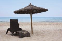 Chaise de plate-forme de plage et parapluie 2 photos stock