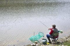 Chaise de Sitting In The de pêcheur sur la ficelle tournoyante de rive et Rod Into The River de lancement photo libre de droits