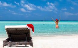 Chaise de Sun avec le chapeau et la fille de Noël dans le bikini sur une plage tropicale Images libres de droits