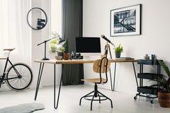 Chaise en bois au bureau avec l'ordinateur de bureau dans l'espace de travail lumineux i Images libres de droits