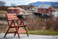Chaise en bois rouge dans le petit village norvégien Photographie stock