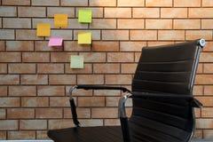 Chaise en cuir noire de bureau devant le mur de briques Photos stock
