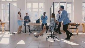 Chaise enthousiaste d'équitation de femme d'affaires d'amusement de mouvement lent le long du grand bureau célébrant la promot clips vidéos
