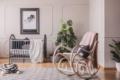 Chaise et affiche de basculage dans l'intérieur de la chambre à coucher de l'enfant gris avec l'usine et la couverture sur le ber photos stock
