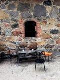 Chaise et table de fer à l'extérieur du vieux bâtiment Photo libre de droits