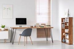 Chaise grise au bureau avec le moniteur d'ordinateur dans l'espace de travail minimal dedans Image stock