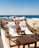 Chaise longs on the beach. White chaise longs on the rocky beach. Samos Island, Greece stock photos