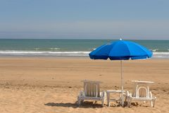 Chaise-longue. And unbrella on coast line Stock Images