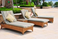 Chaise longue. Picture of three chaise longues beside swimming pool royalty free stock photography