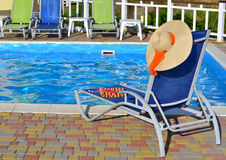 Chaise-longue and beach accessories. Chaise-longue and beach accessories near the pool stock photo