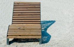 Chaise longue di legno che stanno sulla ghiaia bianca nella città fotografia stock