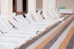 Chaise-longue. Many white empty chaise-longue stock photo
