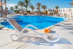 Chaise-longue op de achtergrond van de pool bij het hotel Stock Fotografie