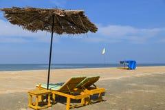 Chaise longue sotto l'ombrello sulla riva del Mar Arabico Fotografie Stock Libere da Diritti