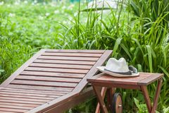 Chaise-longue, table, white hat outdoor. Garden, , on natural green background stock photo