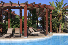 Chaise longue under a canopy near the pool. Stock Images