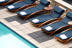 Chaise Longues. Stylish cushioned chaise longues around a modern pool on a rooftop stock photos
