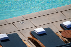 Chaise Longues. Stylish cushioned chaise longues around a modern pool on a rooftop stock photo