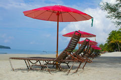 Chaise longues on beach. Row of chaise longues on beach Royalty Free Stock Image