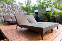 Chaise-longues in de tuin naast zwembad Stock Foto