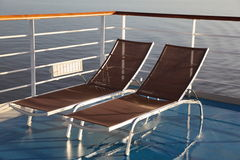 Chaise longues on deck of cruise ship. Two chaise longues on deck of cruise ship. golden morning sun shining royalty free stock photo