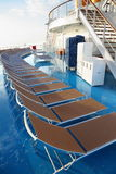 Chaise longues on deck of cruise ship. Row of chaise longues on deck of cruise ship. golden morning sun shining stock photo