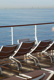 Chaise longues on deck of cruise ship. Many chaise longues on deck of cruise ship in out of focus. buildings far away royalty free stock images
