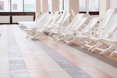 Chaise longues. Many white empty chaise longues stock image