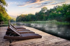 Chaise longues near river. Wicker chaise longues near river at foggy sunrise stock images