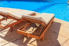 Chaise longues near swimming pool. Concept of spa, rest, relaxation, holidays, resort. Chaise longues near a swimming pool. Concept of spa, rest, relaxation royalty free stock images
