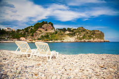 Chaise longues on a pebble beach Stock Image