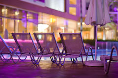Chaise-longues by the pool in the evening Stock Photography
