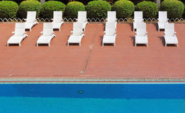 Chaise longues by swimming-pool Royalty Free Stock Images