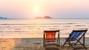 Chaise-lounge alla spiaggia al tramonto nave fotografie stock
