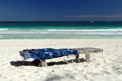 Chaise Lounge on the Beach. An empty chaise lounge and beach towel on a white sand beach, brilliant turquoise water in the background Royalty Free Stock Photography